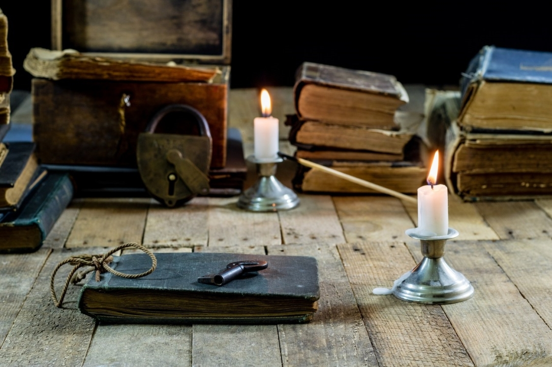Old books and candles on a wooden table. Old room, reading room. Black background